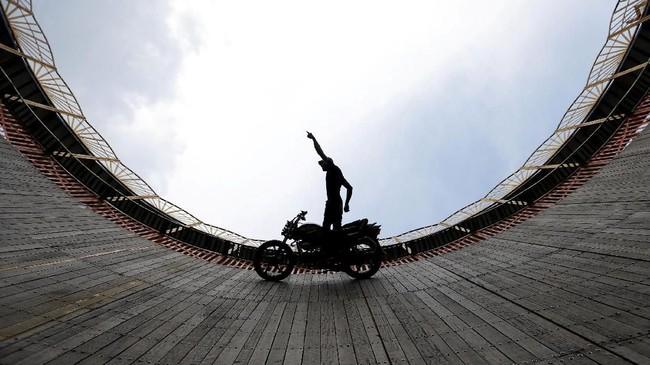 Seorang aktor pemeran penganti beraksi di atas motor di dalam arena