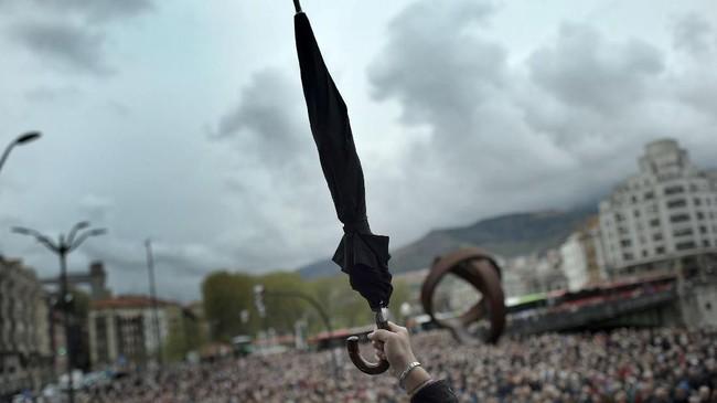 Seorang pensiunan mengangkat payungnya ketika berdemonstrasi menuntut upah hari tua yang lebih baik di Bilbao, Spanyol. (REUTERS/Vincent West)