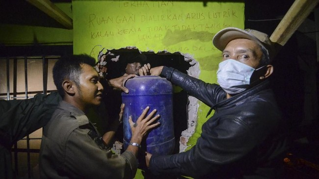 Petugas membawa jerigen yang berisi bahan untuk miras oplosan saat melakukan penggerebekan di Cicalengka. (ANTARA FOTO/Raisan Al Farisi/foc/18.).