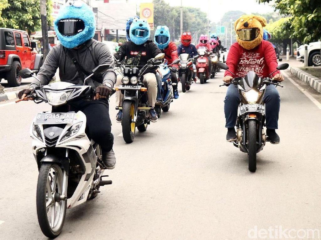 Belasan pengendara sepeda motor konvoi dengan memakai helm elmo.