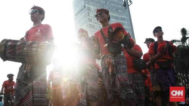 Tak peduli matahari terik, mereka meliuk di antara pejalan kaki yang menikmati CFD. (CNN Indonesia/Andry Novelino)