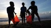 Tak hanya orang dewasa, anak-anak pun ikut bergotong royong membersihkan tumpukan sampah di Pantai Sanur.(Anadolu Agency/Mahendra Moonstar)