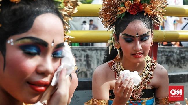 Mereka yang lelah dan butuh beristirahat duduk ala kadarnya di pinggir jalan, demi memamerkan tarian Bali yang atraktif dengan busana warna mencolok, biru dan merah. (CNN Indonesia/Andry Novelino)