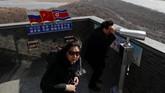 Turis bisa menggunakan teropong untuk mengintip Korea Utara dari sebuah menara yang dibangun di sisi China di perbatasan China, Rusia dan Korut di Kota Hunchun, China. (REUTERS/Damir Sagolj)