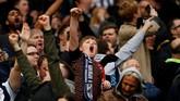 Suporter cilik West Bromwich Albion mengenakan syal saat mendukung tim kesayangannya di Stadion Old Trafford. West Brom menang 1-0 atas Manchester United. (Reuters/Jason Cairnduff)
