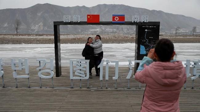 Warga berpose dengan latar belakang Korut di Tumen, China. Di Kota Dandong, tanda yang menunjukkan Korea Utara dapat ditemukan di mana-mana. (REUTERS/Damir Sagolj)