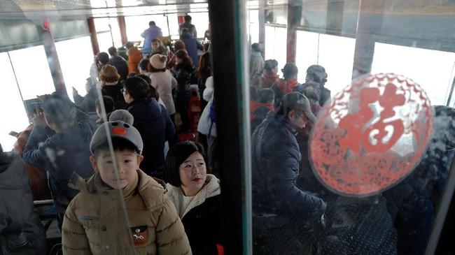 Wisatawan naik kapal dari Sungai Yalu di sisi China untuk menyaksikan tepian sungai di sisi Korea Utara, dekat Dandong, Provinsi Liaoning, China. (REUTERS/Damir Sagolj)