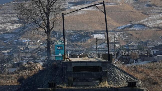 Penjaga perbatasan Korut dipotret dari sisi China di Kota Dandong, di tepi Jembatan Patah Hekou, Sungai Yalu, utara kota Sinulju, Korut. (REUTERS/Damir Sagolj)