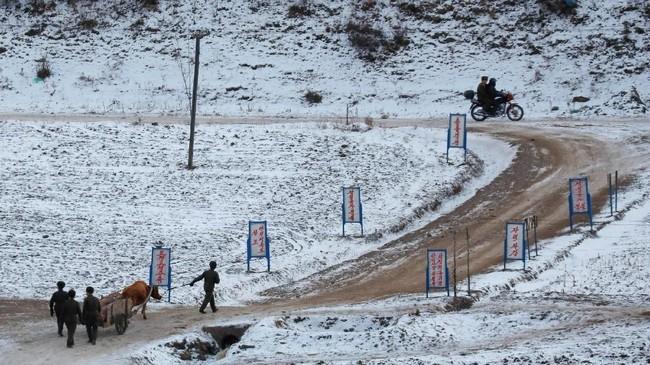 Warga Korea Utara dipotret dari sisi perbatasan China, di perbatasan Changbai, China saat melintasi sebuah desa di Hyesan, Korea Utara. (REUTERS/Damir Sagolj)