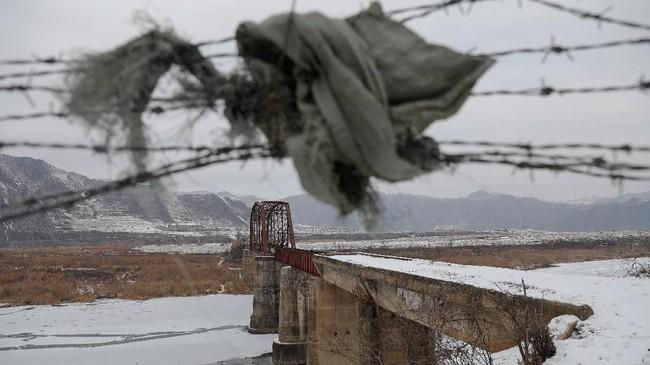 Sobekan kain digunakan untuk membuat celah pada kawat berduri di dekat jembatan tertutup di atas Sungai Yalu di sisi perbatasan China dengan Korea Utara antara Kota Ji'an dan Linjiang, China. (REUTERS/Damir Sagolj