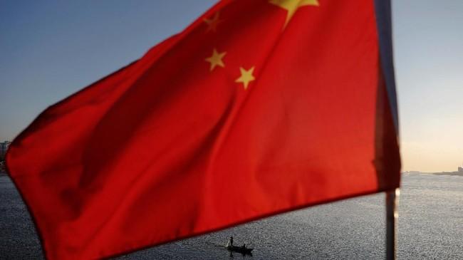 Nelayan Korut tampak di tengah kibaran Bendera China di Jembatan Patah di tengah temaram cahaya matahri terbenam di Sungai Yahlu di perbatasan Kota Sinulju dan Dandong, Provinsi Liaoning, China. (REUTERS/Damir Sagolj)