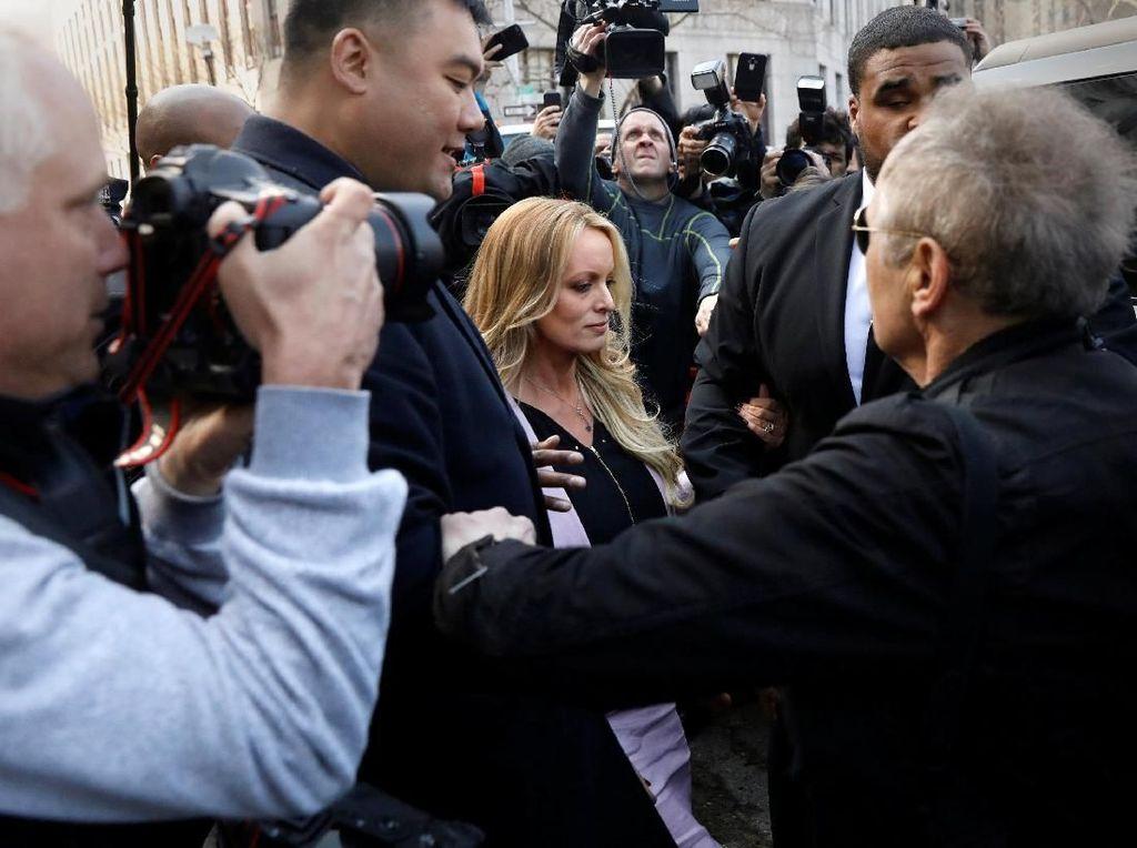 Daniels masih diikuti kamera wartawan saat akan kembali ke mobilnya untuk meninggalkan gedung pengadilan. Foto: REUTERS/Brendan McDermid