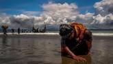 Usai menyelamatkan diri dari Myanmar dengan mengendarai perahu, seorang wanita tiba di pantai di Shah Porir Dwip, Bangladesh pada 11 September 2017 dalam kondisi dehidrasi setelah berhari-hari terombang-ambing di lautan menghindari upaya genosida. (REUTERS/Danish Siddiqui)