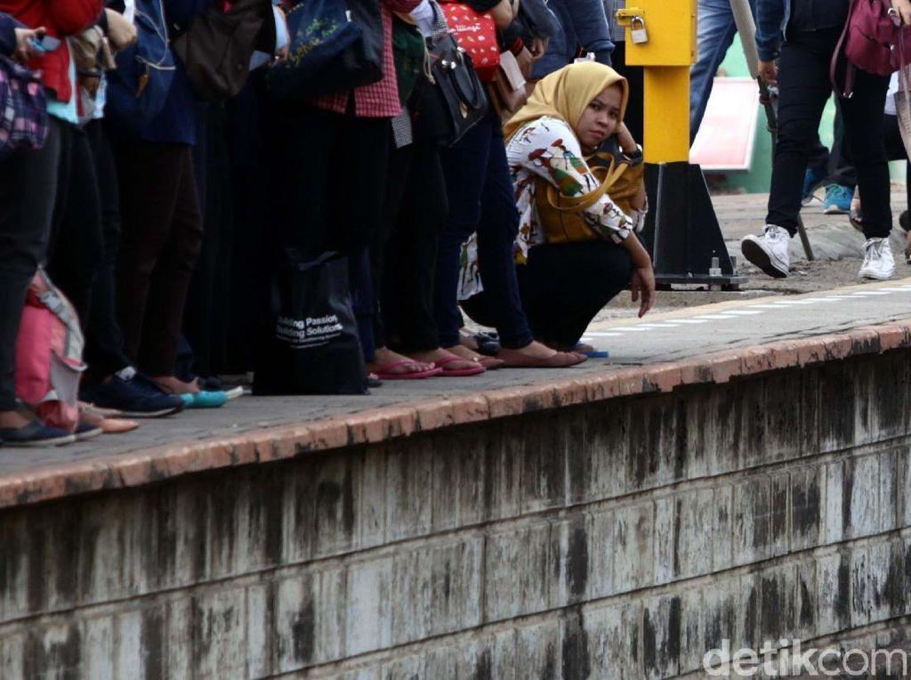 Lelah berdiri, seorang penumpang jongkok saat menunggu datangnya kereta.