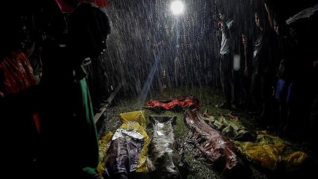 Orang-orang berkumpul di tengah hujan deras mengelilingi mayat pengungsi Rohingya yang diturunkan dari kapal pelarian mereka dari Myanmar. Mereka mendarat di Pantai Inani dekat Cox's Bazar, Bangladesh, 28 September 2017. (REUTERS/Damir Sagolj)