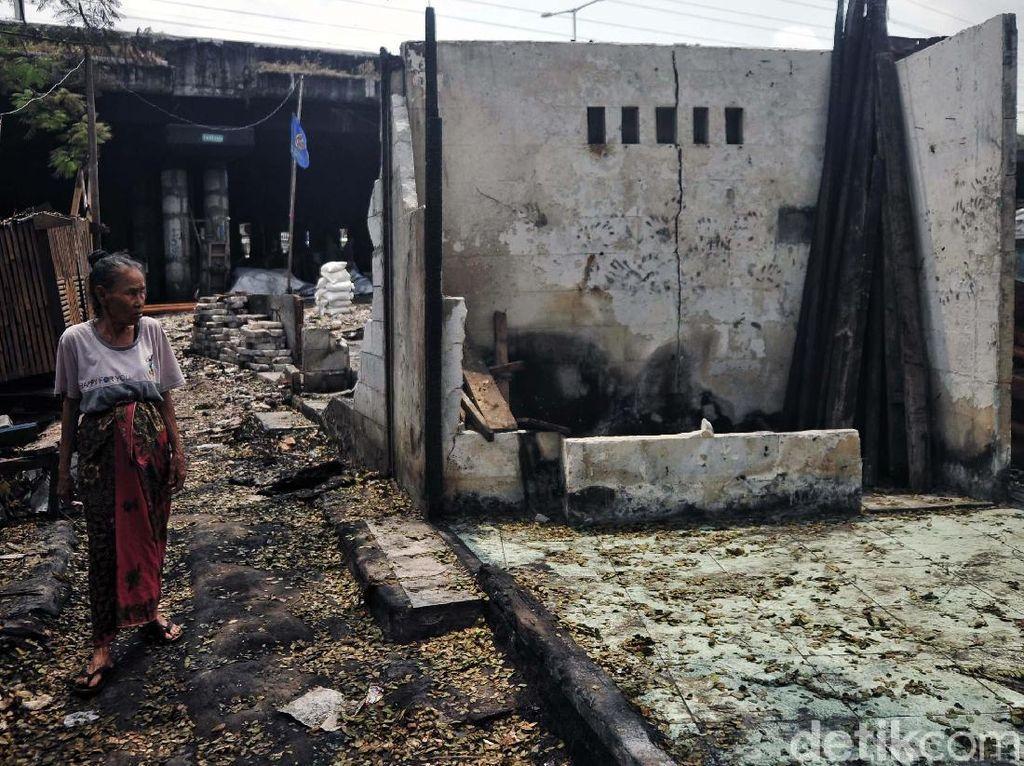 Seorang ibu melihat rumahnya yang ludes terbakar.