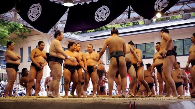 Ribuan penonton disuguhi pameran pertarungan, yang didahului dengan upacara pengentakan kaki yang dihormati sepanjang zaman, juga nyanyian tradisional dan bahkan sebuah rutinitas komedi yang menjelaskan peraturan gulat sumo. (REUTERS/Toru Hanai)