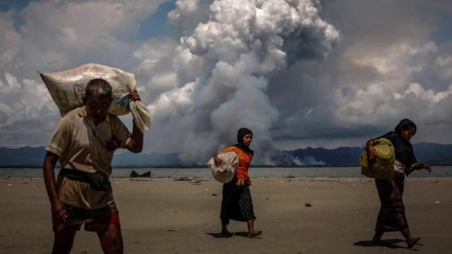 Asap membubung tinggi di perbatasan Myanmar ketika pengungsi Rohingya berjalan di pantai setelah melewati perbatasan Myanmar dan Bangladesh pada 11 September 2017. Eksodus besar-besaran warga Rohingya dari Myanmar ke sejumlah negara di sekitarnya menarik perhatian dunia. (REUTERS/Danish Siddiqui)