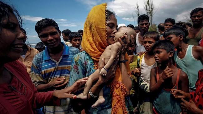 Hamida, seorang wanita pengungsi Rohingya, menangis ketika mengangkatmayat bayi laki-lakinya yang baru berusia 40 hari. Putranya meninggal di kapal ketika melarikan diri dari Myanmar dan tiba di Shah Porir Dwip, Teknaf, Bangladesh, 14 September 2017. (REUTERS/Mohammad Ponir Hossain)