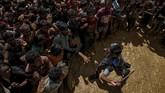 Seorang petugas keamanan berupaya menertibkan pengungsi Rohingya yang melarikan diri dari Myanmar di pasar Cox, Bangladesh, 21 September 2017. (REUTERS/Cathal McNaughton)