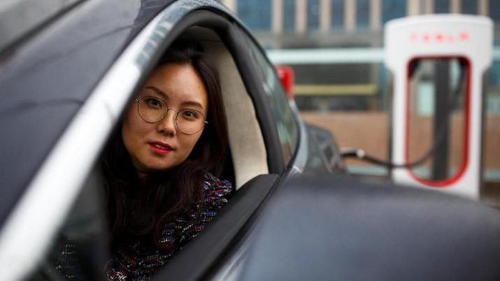 Zang Yi berpose untuk gambar saat mobil Tesla-nya sedang mengisi di titik pengisian daya di Beijing, China, 13 April 2018. Zang mengatakan jika ketegangan perdagangan menghasilkan impor AS yang lebih mahal, dia tidak akan mempertimbangkan merek Amerika ketika saatnya tiba. membeli sebuah mobil baru.