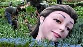 Menggunakan rangkaian bunga-bunga tulip, seorang pekerja sedang menyelesaikan instalasi seni berupa kepala raksasa di kubah Gardens by the Bay di Singapura, jelang dibukanya festival tahunan bunga tulip di sana. (AFP PHOTO / Roslan RAHMAN).