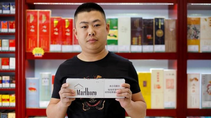 Shan Yuliang, penjual di sebuah toko rokok dan anggur, berpose dengan sekotak rokok Marlboro di Beijing, China, 8 April 2018.