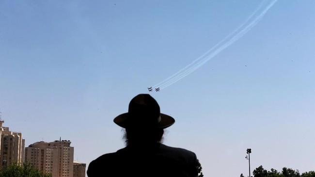 Seorang penganut agama Yahudi Ultra Ortodoks memandang pasukan udara Israel yang sedang latihan terbang akrobat jelang pertunjukan udara di hari kemerdekaan Israel ke-70, di Yerusalem. (REUTERS/Ammar Awad)