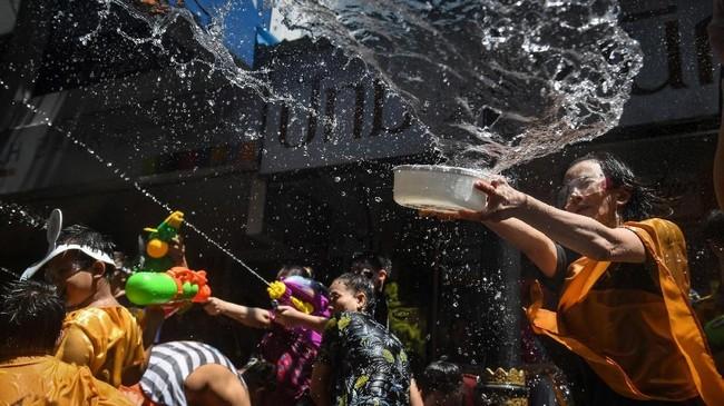 Peserta festival air Songkran saling melemparkan air satu sama lain. Festival Songkran sendiri digelar selama satu pekan untuk merayakan tahun baru tradisional di Thailand. (AFP PHOTO / LILLIAN SUWANRUMPHA)