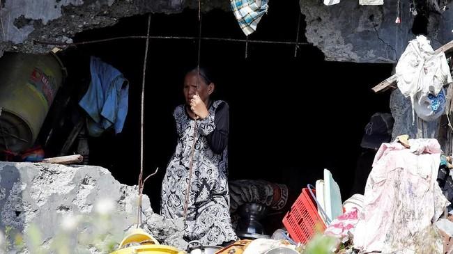 Sebagian warga lain hanya bisa terperangah melihat tentara mengangkat sisa potongan tubuh korban perang yang menewaskan 1.200 orang tersebut. (Reuters/Erik De Castro)