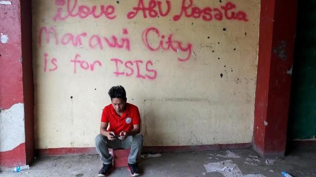 Ketika orang sibuk mencari sisa harta benda, satu warga terlihat hanya termenung karena butiknya kini sudah rata dengan tanah, hanya tersisa tembok yang dicoreti tulisan ISIS. (Reuters/Erik De Castro)