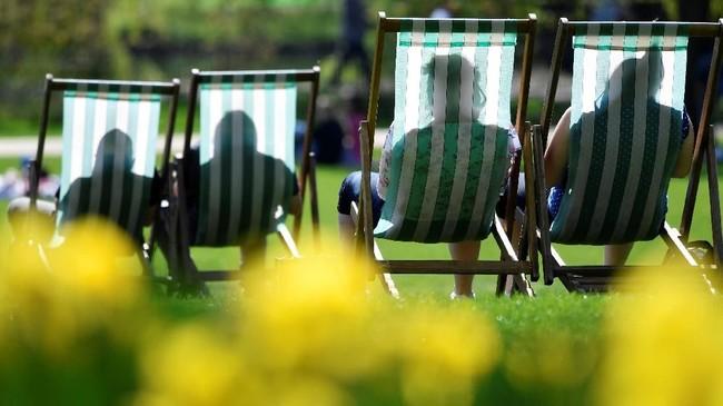 Bayangan orang yang sedang menikmati sinar matahari terlihat dari balik kursi santai di taman St. James di London, Inggris. (REUTERS/Toby Melville)