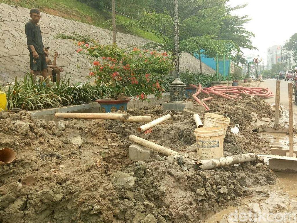 Foto: Beberapa pekerja mulai mengumpulkan karung yang berisi tanah di antara trotoar dan jalanan untuk dirapikan. (Raja Adil Siregar-detikcom)