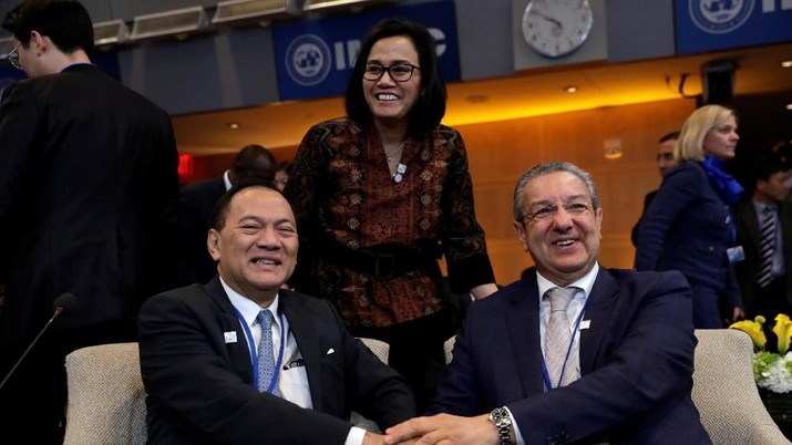 Indonesian Finance Minister Sri Mulyani (C) smiles as Indonesia's Central Bank Governor Agus Martowardojo (L) shakes hands with Bank of Algeria governor Mohamed Loukal at IMFC plenary during the IMF/World Bank spring meeting in Washington, U.S., April 21, 2018. REUTERS/Yuri Gripas