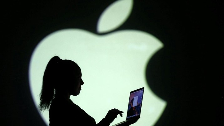 REFILE - CLARIFYING CAPTION Silhouette of laptop user is seen next to a screen projection of Apple logo in this picture illustration taken March 28, 2018.  REUTERS/Dado Ruvic