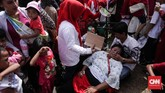 Riuhnya acara membuat sejumlah warga tampak tak sadarkan diri. Seorang warga pingsan saat berebut untuk keluar dari kawasan Monas di gelaran 'Untukmu Indonesia'. (CNN Indonesia/ Hesti Rika)