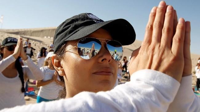 Beberapa peserta menggunakan kaca mata untuk menahan sengatan matanya dari terik sinar matahari ketika melakukan aktivitas yoga.