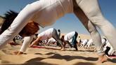 Semua peserta latihan yoga tak menggunakan alas kaki. Mereka berdiri, duduk, danmerundukkan tubuh di bawah terik sinar matahari.