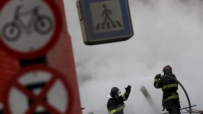 Siaran langsung di televisi sempat menunjukkan seorang lelaki di gedung tersebut, mencoba menyelamatkan diri dengan tali penyelamat dan dibantu pemadam kebakaran. (REUTERS/Leonardo Benassatto)