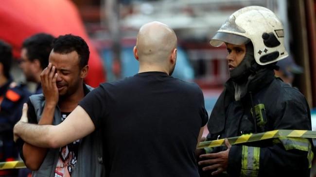 Namun, gedung tiba-tiba ambruk dan orang tersebut menghilang di tengah reruntuhan. Pihak berwenang menduga lelaki itu jadi korban jiwa, meski pencarian masih terus dilakukan. (REUTERS/Leonardo Benassatto)
