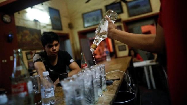Para petani jimador khawatir mesin pada akhirnya bisa menggantikan mereka. Namun, memanen agave dengan mesin akan menjadi rumit, karena sulit untuk memprediksi 'jantung' dari tanaman. Seorang bartender menyajikan tequila di bar La Capilla, Tequila, Meksiko.(REUTERS/Carlos Jasso)