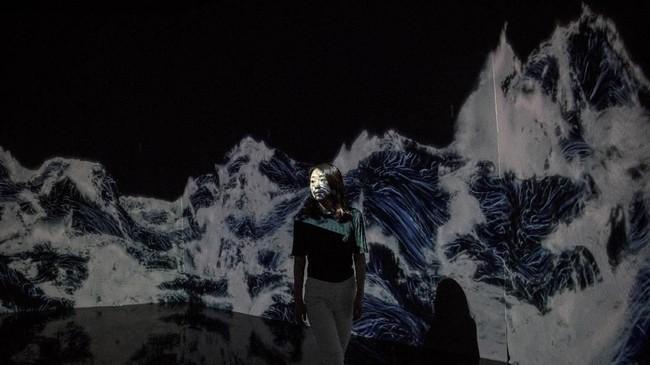 Seorang anggota Teamlab berpose pada sebuah ruangan yang berisikan instalasi digital yang menampilkan deburan ombak yang menabrak tembok. Instalasi digital ini terdapat di Museum Seni Digital Mori di Tokyo. Teamlab terkenal dengan kemahiran memadukan proyeksi gambar, suara, di dalam ruangan. (AFP/Behrouz Mehri)