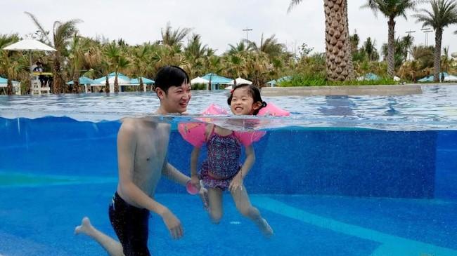 Pengunjung hotel Lin Hongyu berenang dengan putrinya yang berusia tiga tahun di kolam renang resort Atlantis Sanya, Provinsi Hainan, China. (Reuters/Bobby Yip)