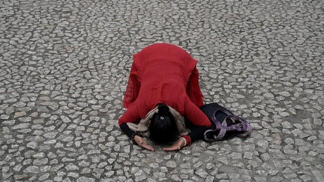 Seorang umat Buddha bersujud di depan situs Sekolah Beichuan yang terkubur dalam bencana gempa pada 2008 di Provinsi Sichuan, China. (Reuters/Jason Lee)