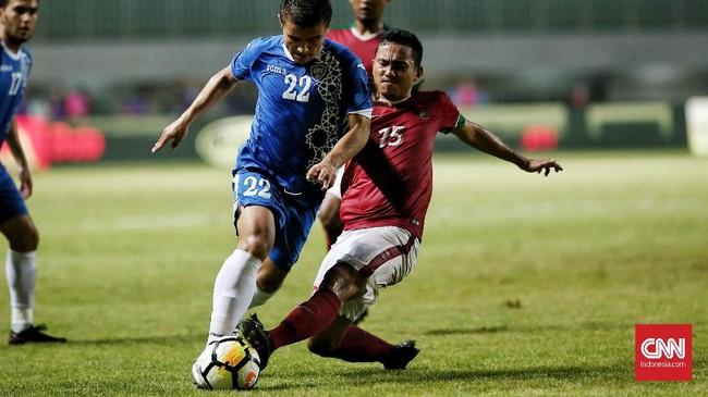 Bek Timnas Indonesia Ricky Fajrin berusaha merebut bola dari kaki pemain timnas Uzbekistan. Timnas Indonesia gagal mencetak gol dari tiga pertandingan PSSI Anniversary Cup 2018. (CNN Indonesia/Andry Novelino)
