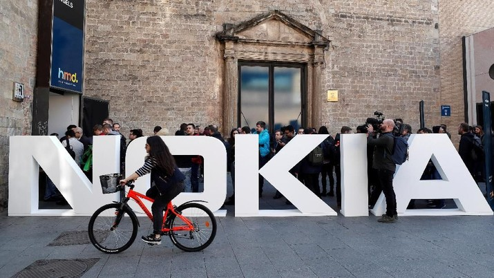 FILE PHOTO: A cyclist rides past a Nokia logo during the Mobile World Congress in Barcelona, Spain February 25, 2018. REUTERS/Yves Herman