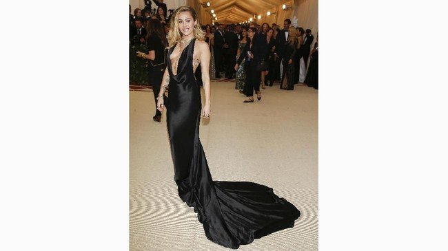 Penyanyi dan penulis laguMiley Cyrus memilih gaun halter neck hitam dengan ekor gaun yang tak terlalu panjang. Dia memakai gaun buatan Stella MacCartney. (REUTERS/Carlo Allegri)
