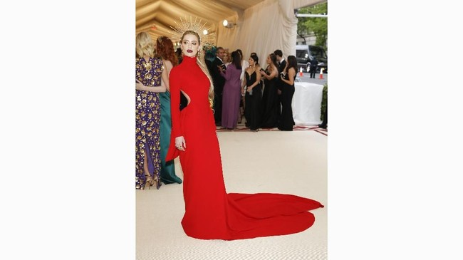 Selain gaun merah mencolok rancangan Carolina Herrera, aktris Amber Heard tampil unik dengan hiasan kepala yang seolah membuatnya 'bersinar'. (REUTERS/Carlo Allegri)