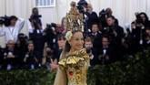 Hampir beberapa tahun belakangan, Sarah Jessica Parker selalu menggunakan headpiece yang mencolok. Tahun ini dengan gaun kuning mengembang dan berekor panjang dari Dolce & Gabbana, SJP memakai hiasan kepala tinggi yang menyerupai gua Maria. (REUTERS/Eduardo Munoz)