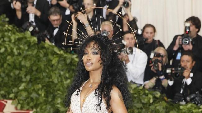 SZA memakai gaun dari Versace ala balerina. Dia juga melengkapinya dengan hiasan kepala setengah lingkaran bergaya celestial. (REUTERS/Carlo Allegri)